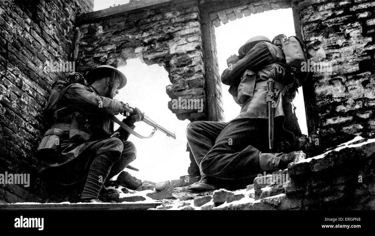WWII - Soldiers in ruined building looking through a window, one pointing a gun, the other looking through binoculars. - Stock Image