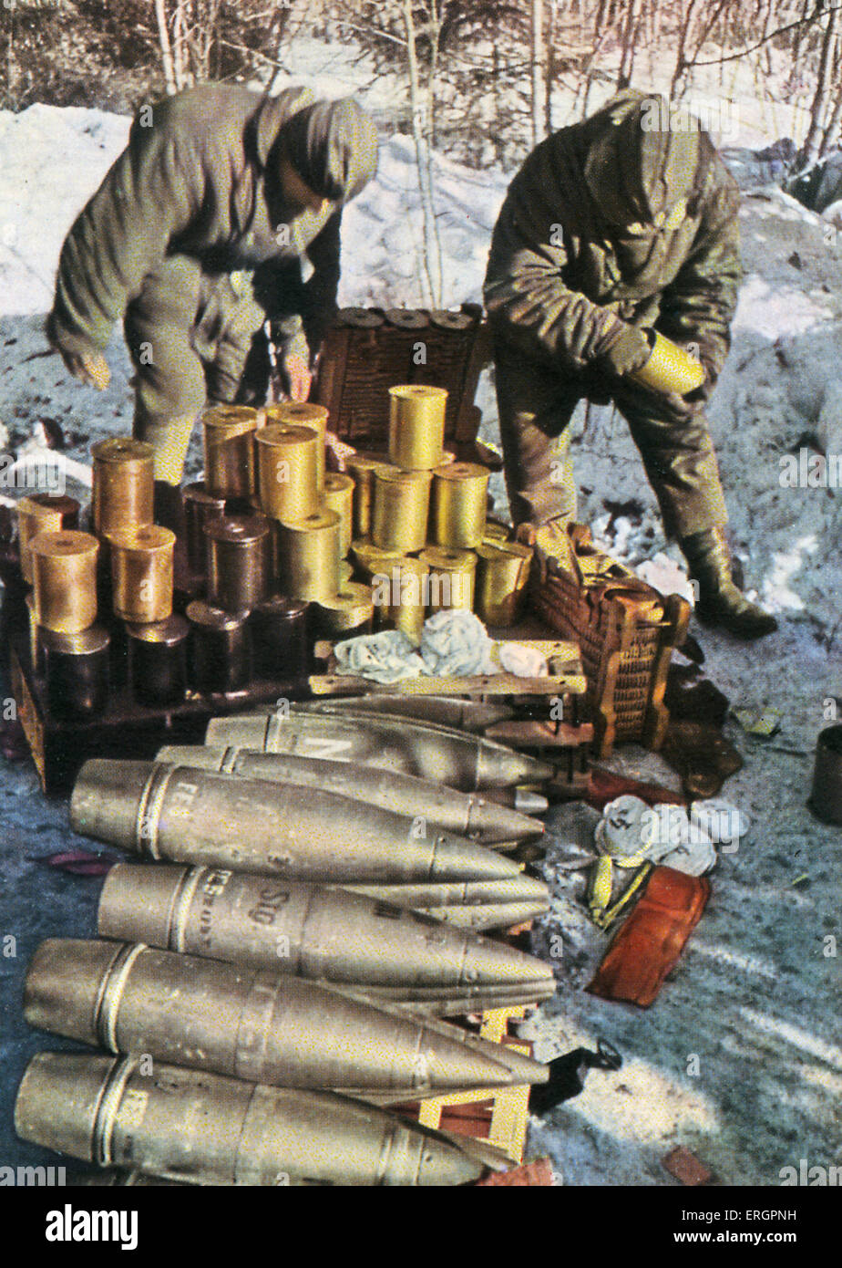 WW2 - Eastern Front, Winter. Two soldiers sort through a large collection of ammunition. - Stock Image