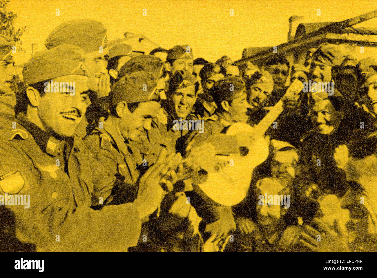 WW2 - Blue Division /  División Azul. A group of soldiers enjoy a song accompanied by guitar. Caption reads: - Stock Image