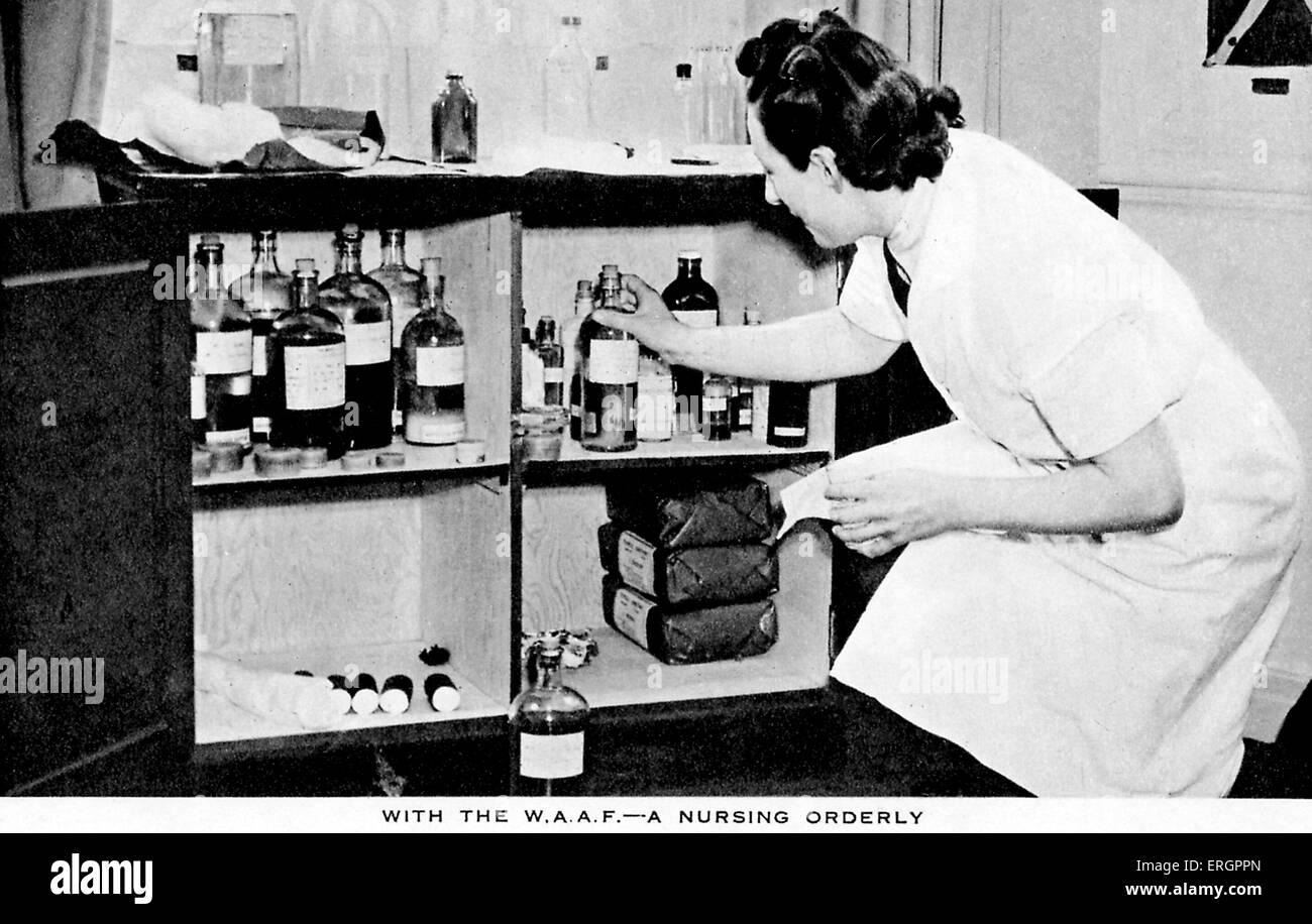 Women 's Auxiliary Air Force (WAAF) - A nurse takes a bottle from a medicine cabinet. - Stock Image