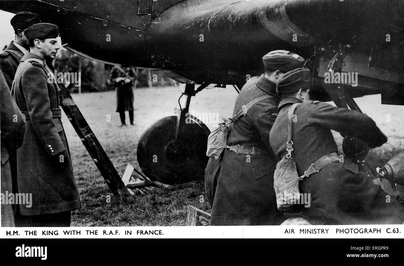 WWII - George VI visits the RAF in France. King George watches two aircraft men attend to a plane. - Stock Image