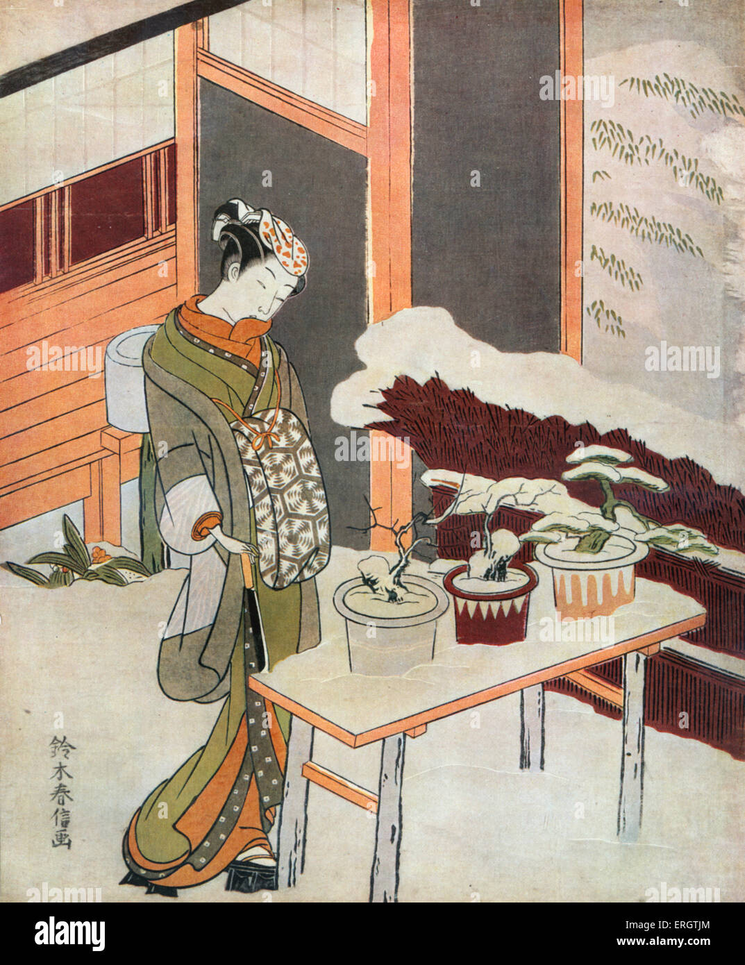 Young Japanese woman in kimono looking down at snow covered plants - print by Suzuki Harunobu, Japanese printmaker - Stock Image