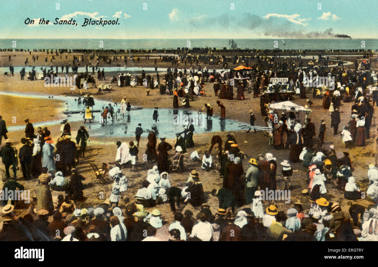 Seaside at Blackpool at turn of the century. families in Edwardian costume, paddling in tide pools of water. Caption - Stock Image