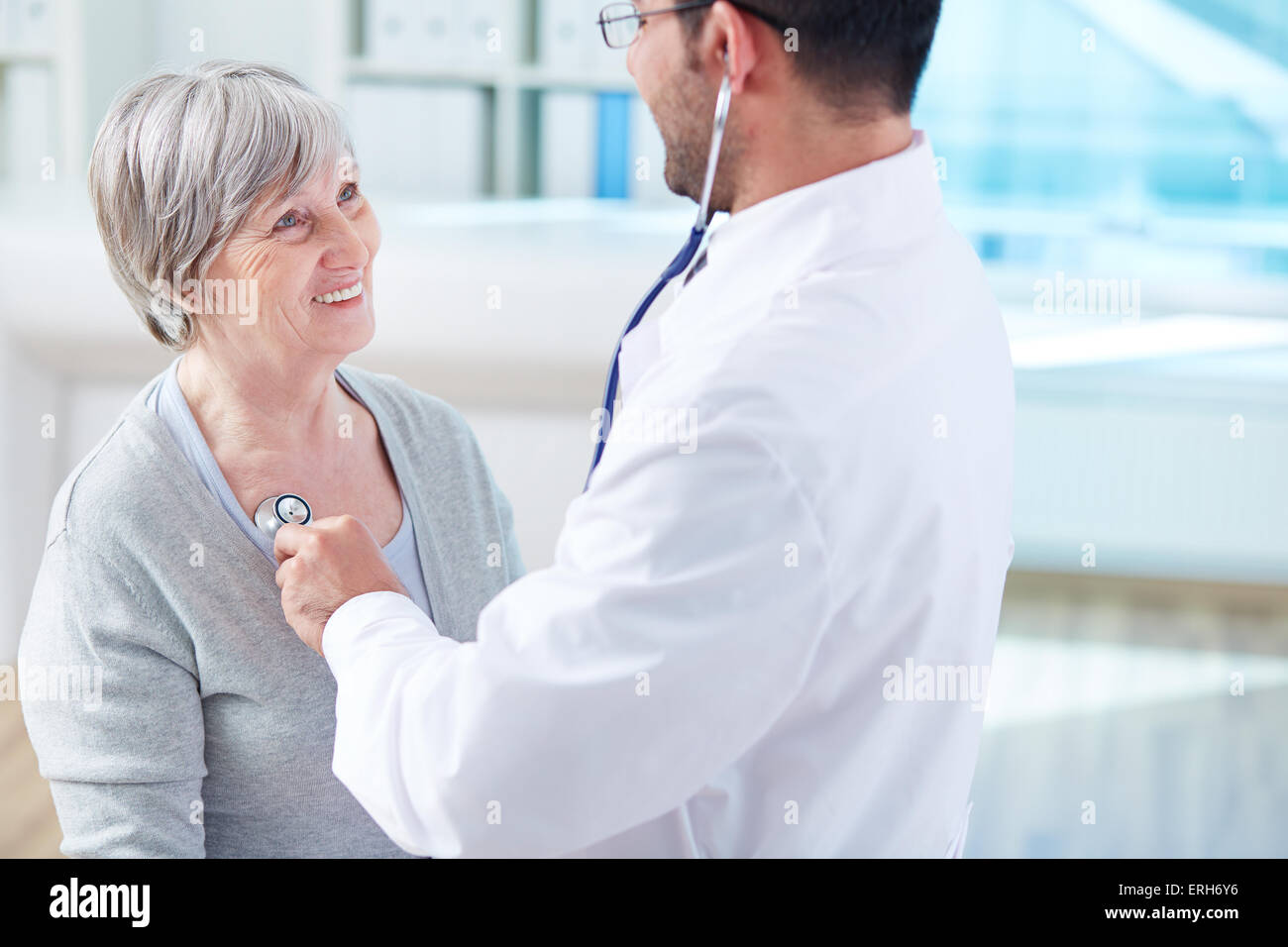 Young doctor treating happy senior patient in hospital - Stock Image