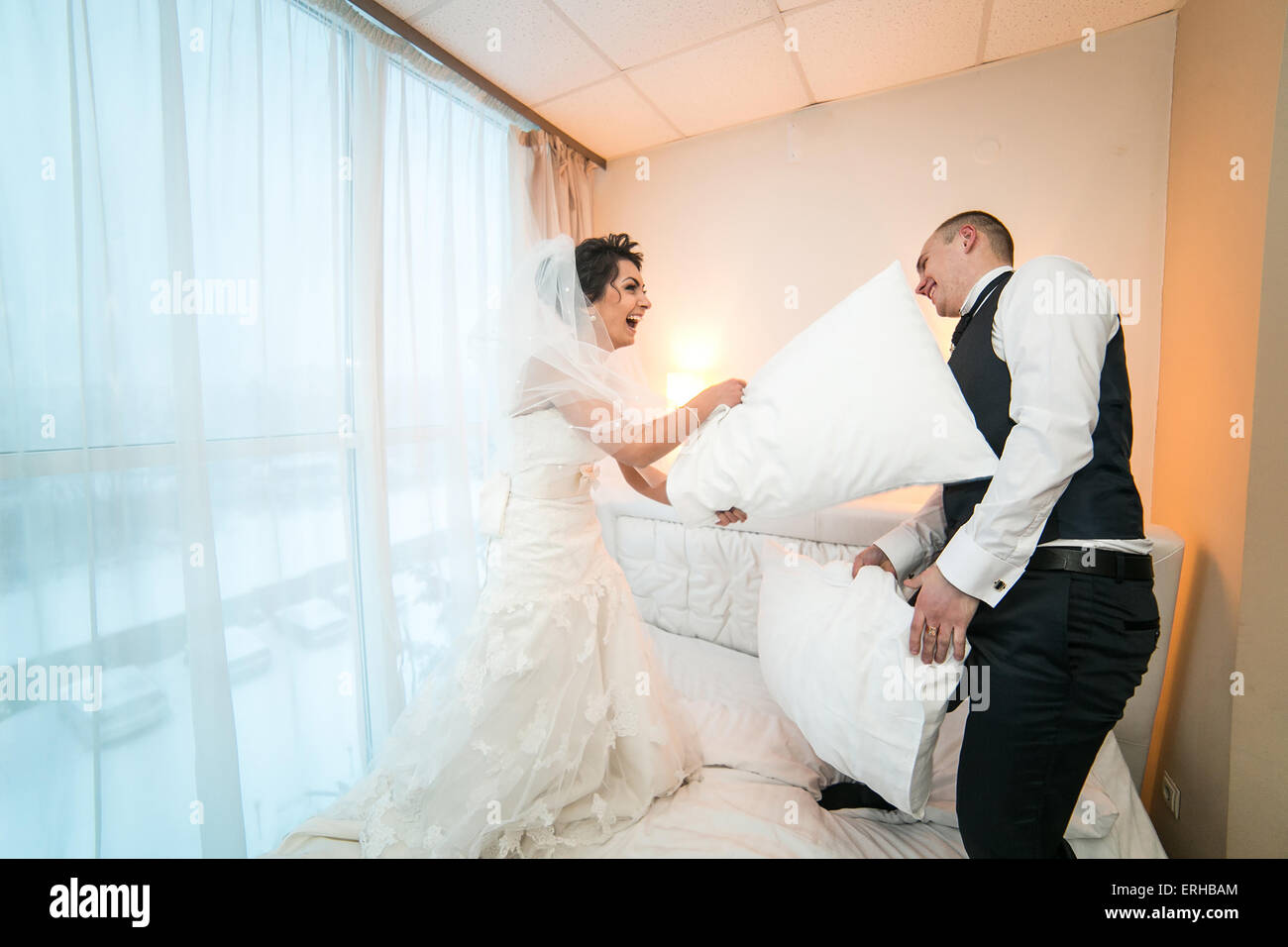 Pillow fight of bride and groom in a hotel room - Stock Image