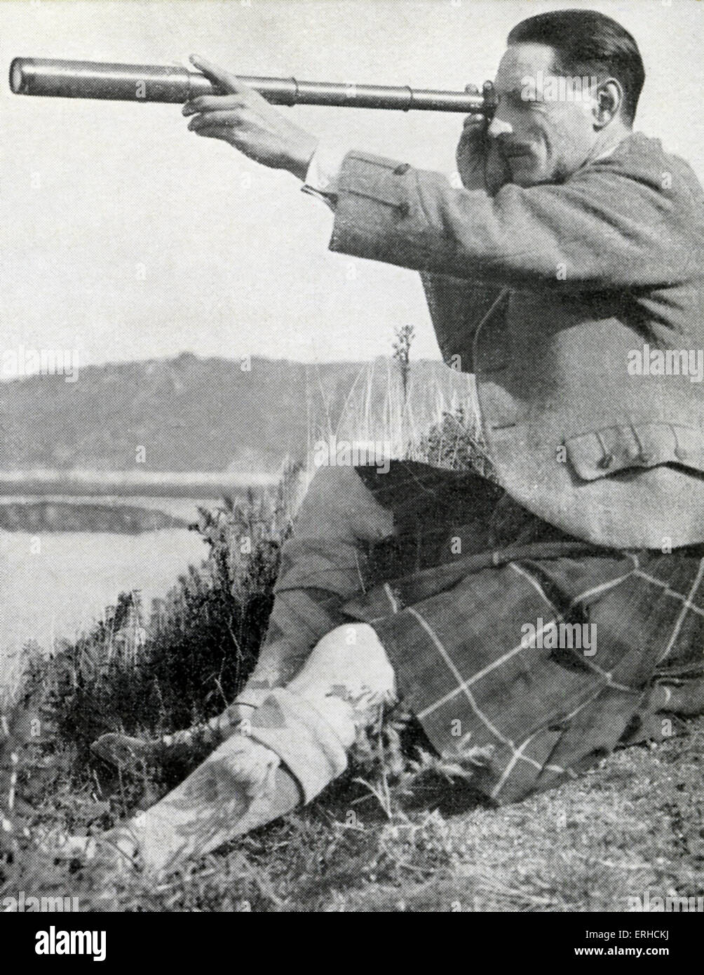 Compton Mackenzie, writer, cultural commentator, raconteur, Scottish nationalist, shown looking through a telescope, - Stock Image