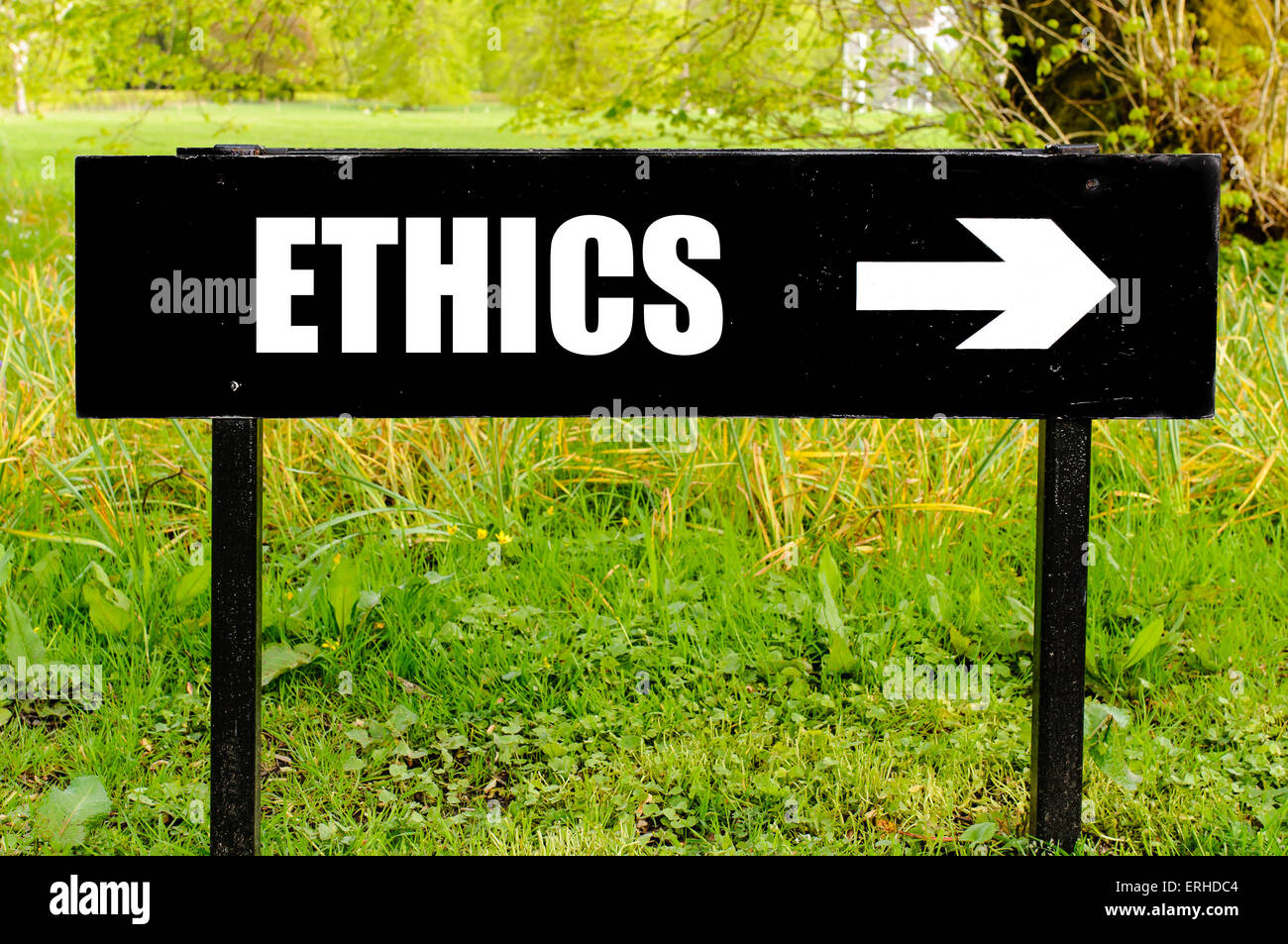 ETHICS written on directional black metal sign with arrow pointing to the right against natural green  background. - Stock Image