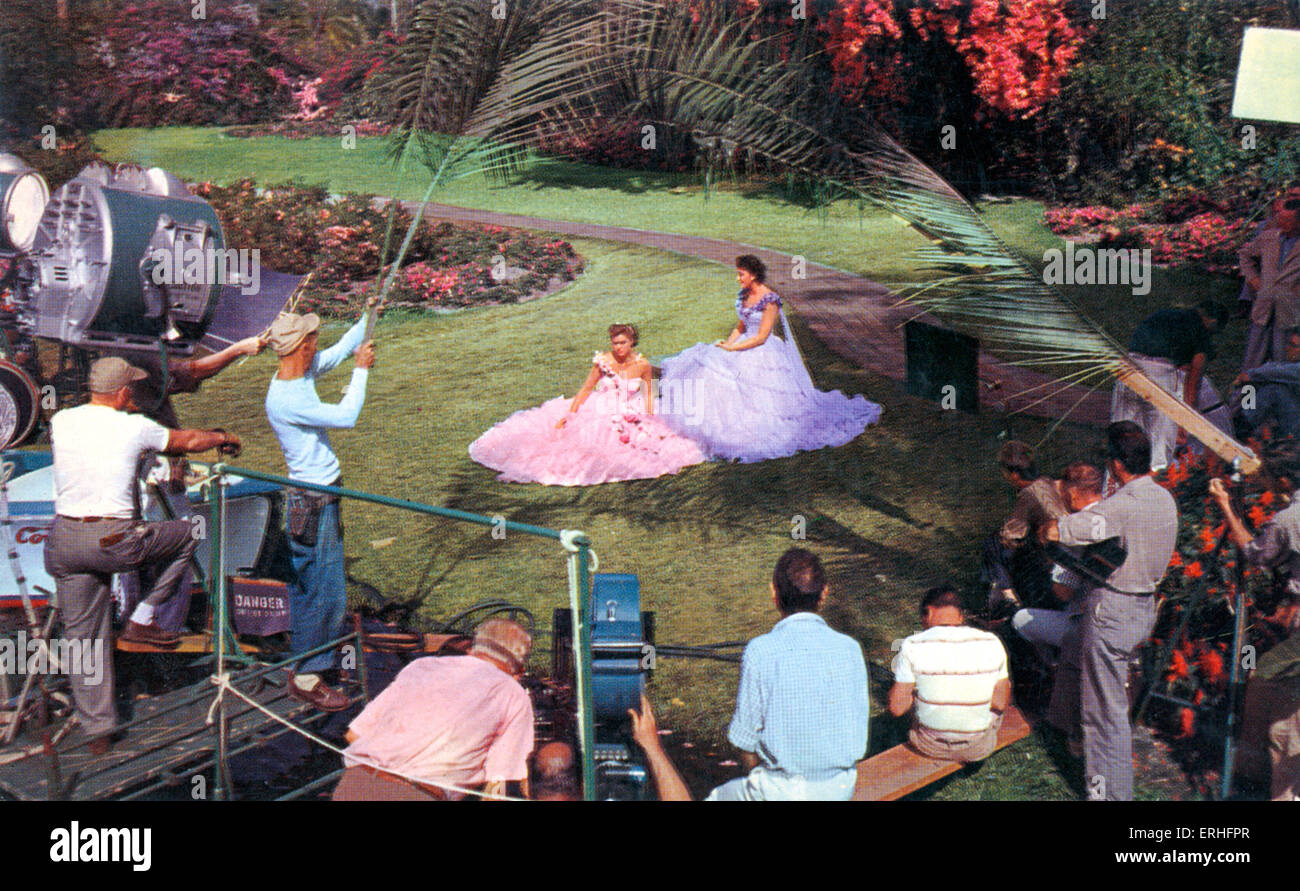 Hollywood movie set. Two unidentified actresses being filmed surrounded by film crew, 1950 s. - Stock Image