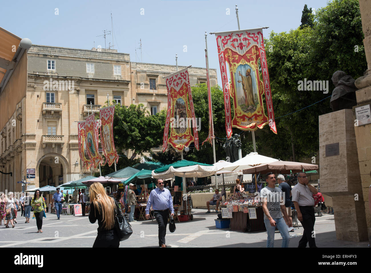 Religious banners dedicated to saints line Republic street in the center of Valletta. Souvenirs are for sale on - Stock Image