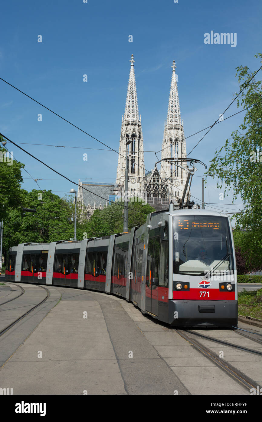 A 7 part low floor articulated tram on route 43 arrives at Schottentor tram halt. The towers of Votive Church are - Stock Image