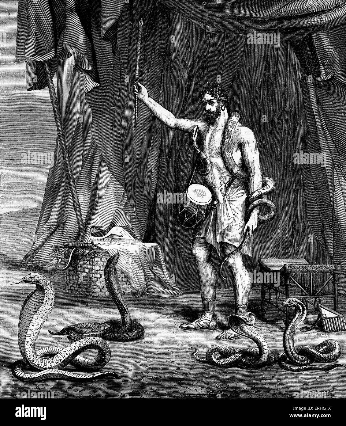 Snake charmer during biblical times surrounded by snakes and holding a drum. - Stock Image