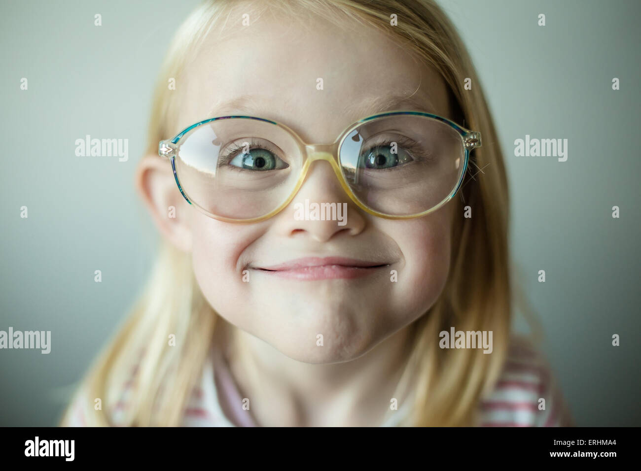 Girl wearing glasses making a silly face - Stock Image