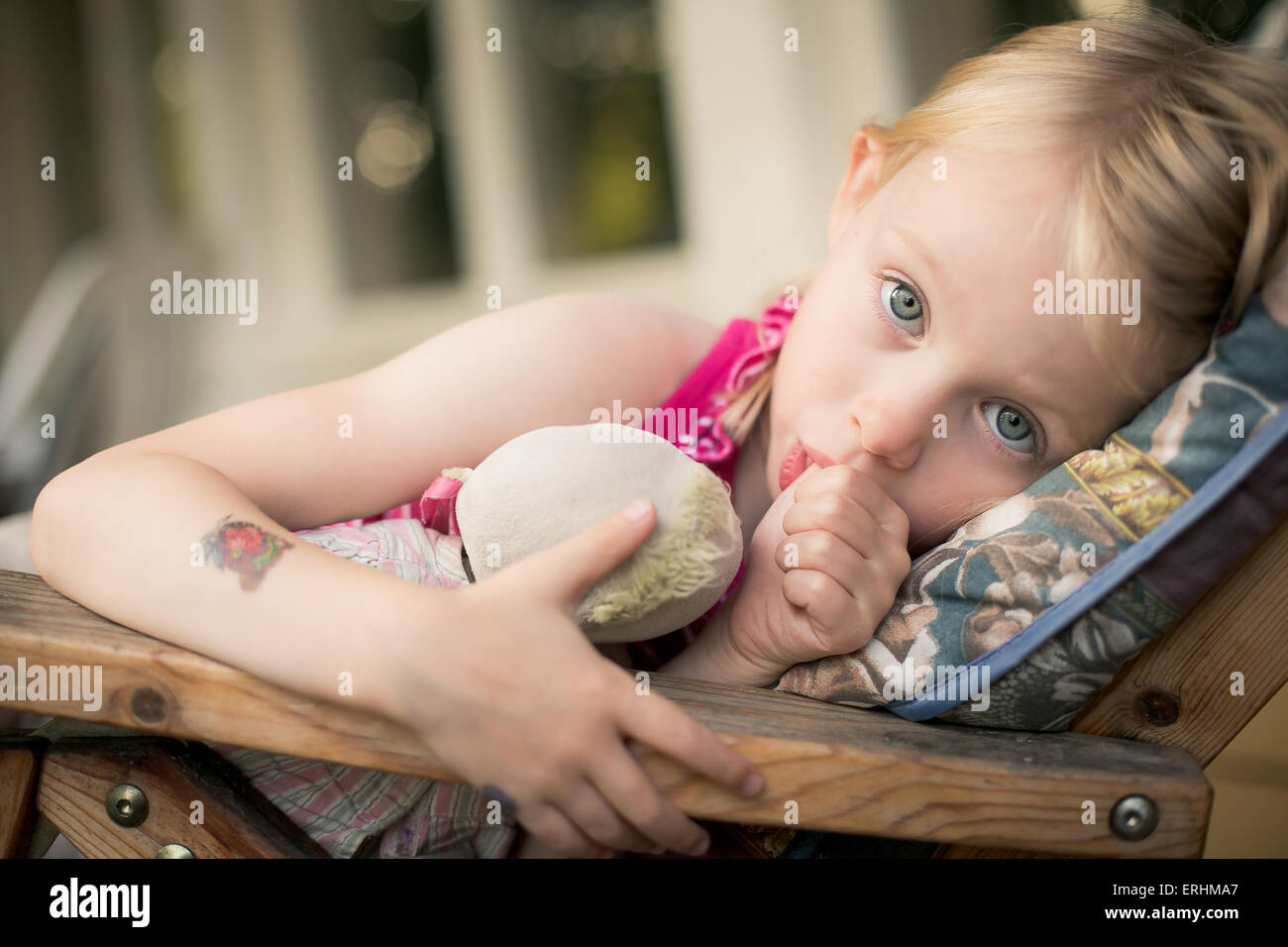 Girl lying in a chair sucking her thumb - Stock Image