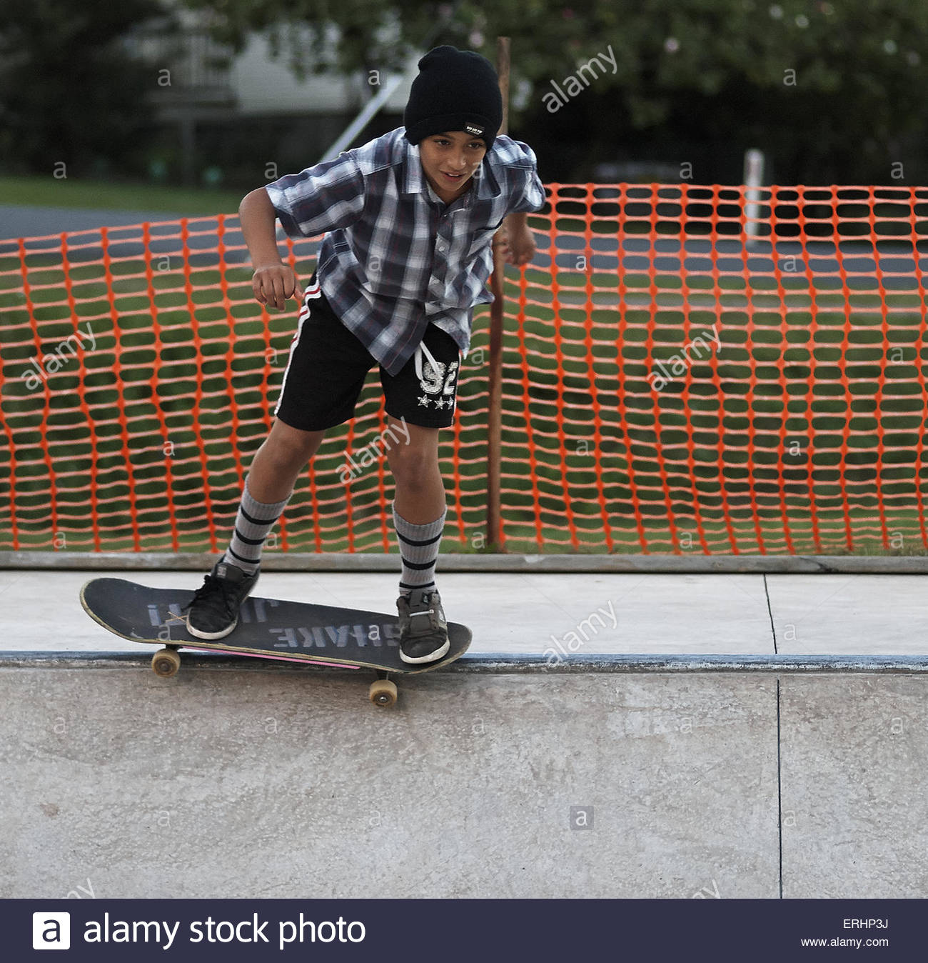 A young Jewish / Israeli boy, skateboarding along the metal lip or coping in the concrete bowl, at the skatepark - Stock Image