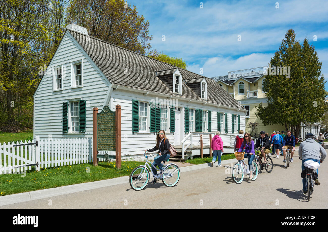 Michigan, Mackinac Island, Market Street, bicyclists pass historic Biddle House - Stock Image