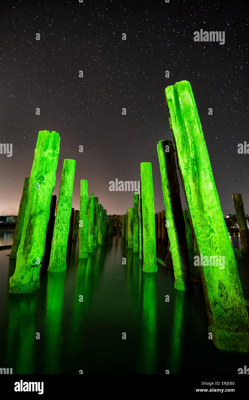 Unusual green poles in the water reflection  at night with deep stars sky - Stock Image
