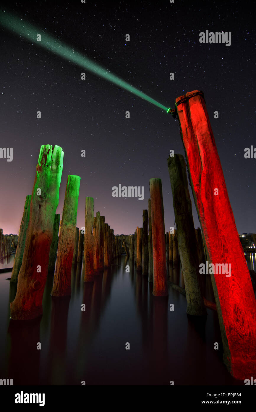 Unusual red poles in the water reflection  at night with deep stars sky - Stock Image