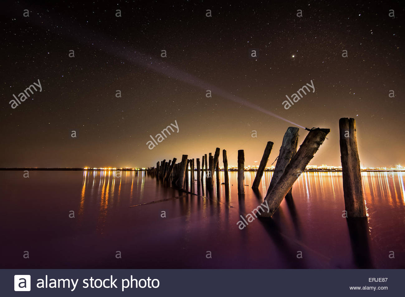 Unusual  pole with beam in the water  at night with deep stars sky - Stock Image