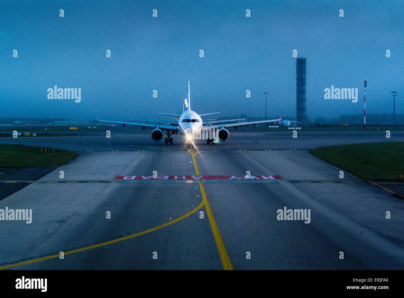 Plane on runway at airport just before takeoff - Stock Image