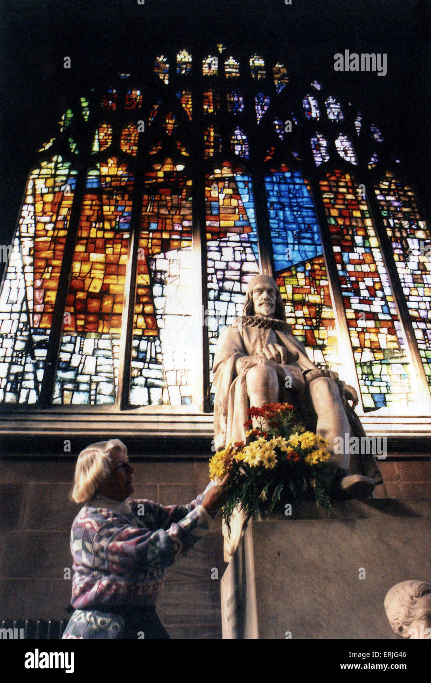 Joan Gage, of Stretford, puts flowers in front of one of the windows at Manchester Cathedral, 9th November 1995. - Stock Image