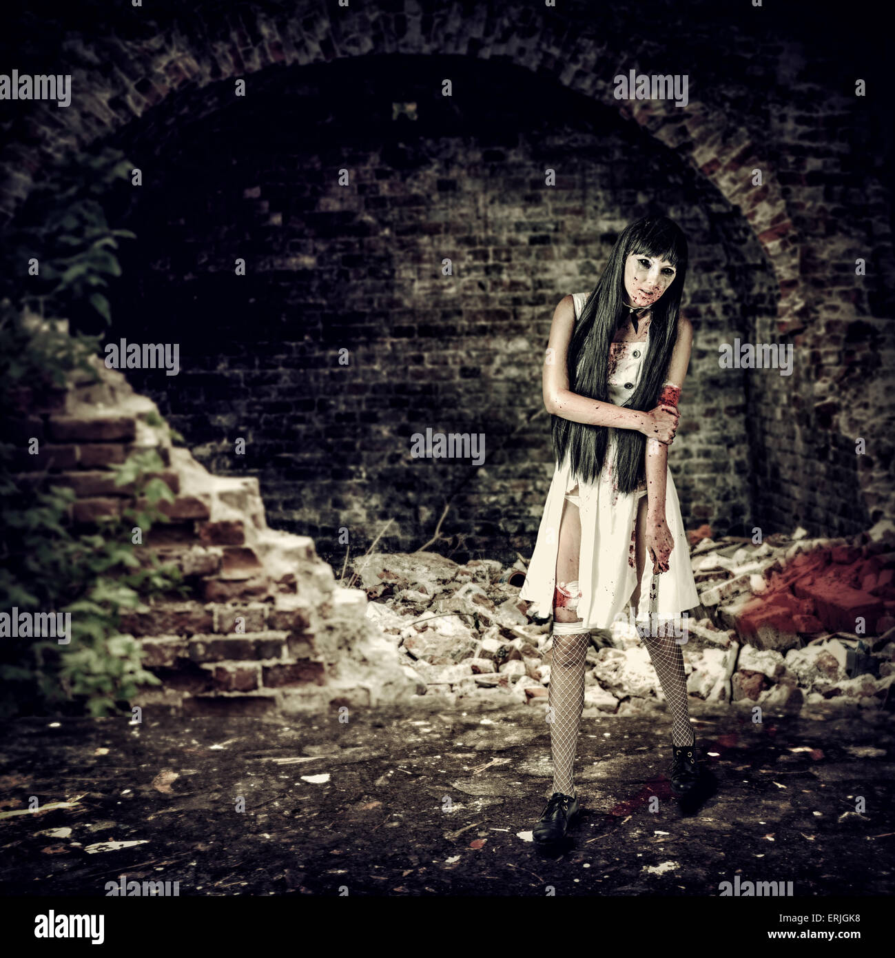 Female zombie with blood holding knife in ruins - Stock Image