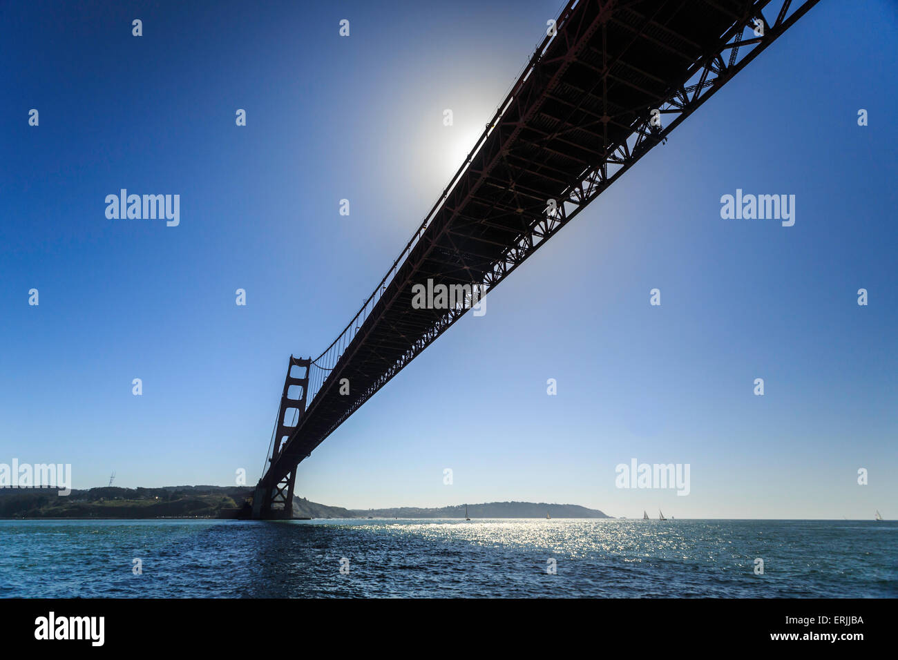 Sun partially blocked by span, of Golden Gate Bridge reflects on San Francisco bay - Stock Image