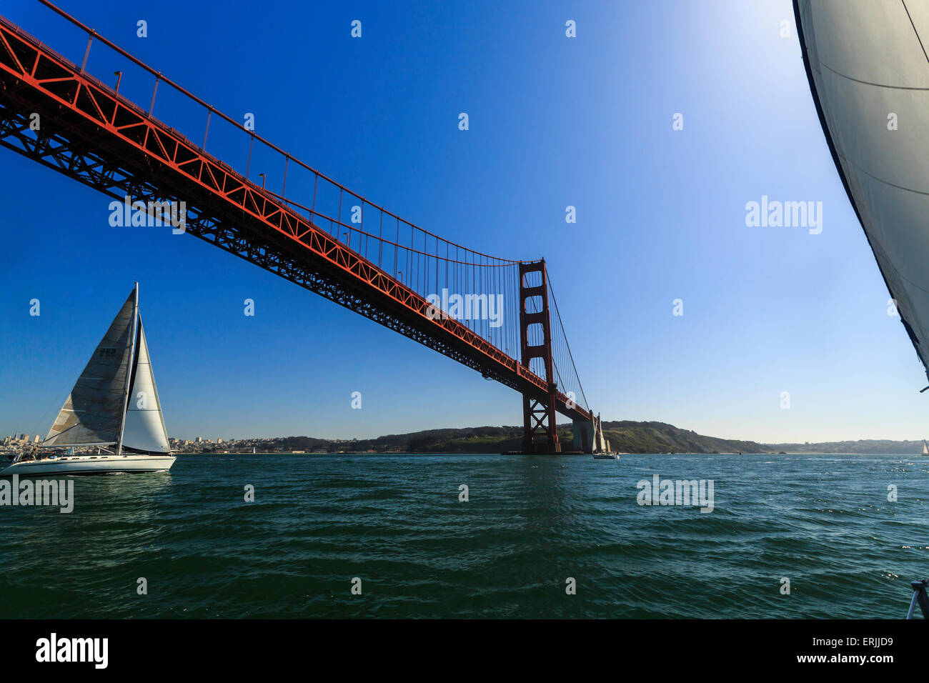 Sailboat passing under the bright red superstructure of the Golden Gate Bridge on a sunny day - Stock Image