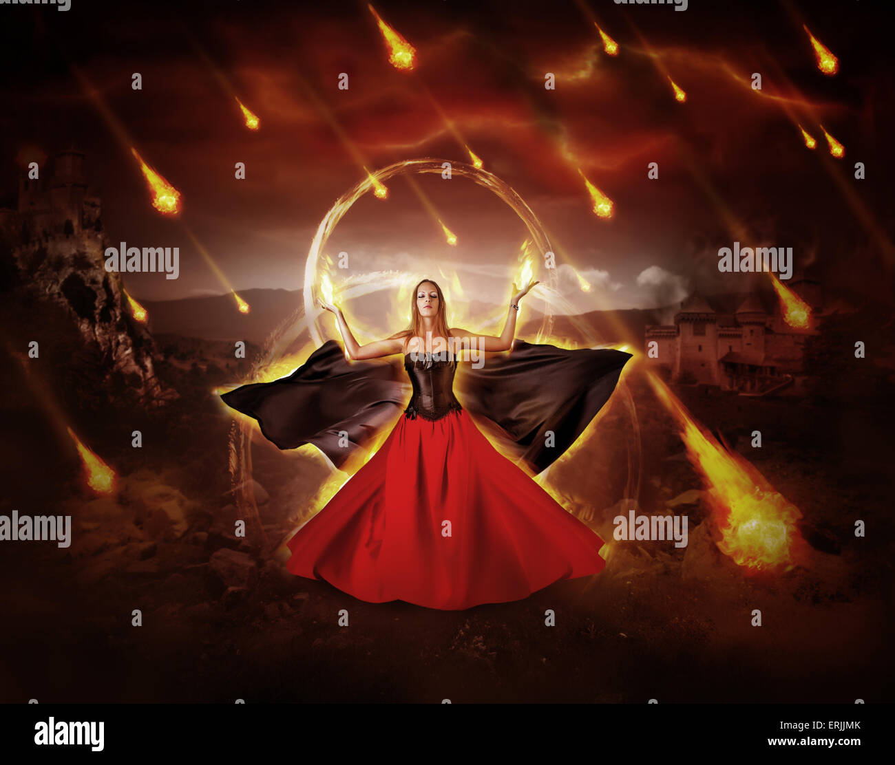 woman fire mage in medieval dress with developing mantle conjured fiery meteor rain - Stock Image