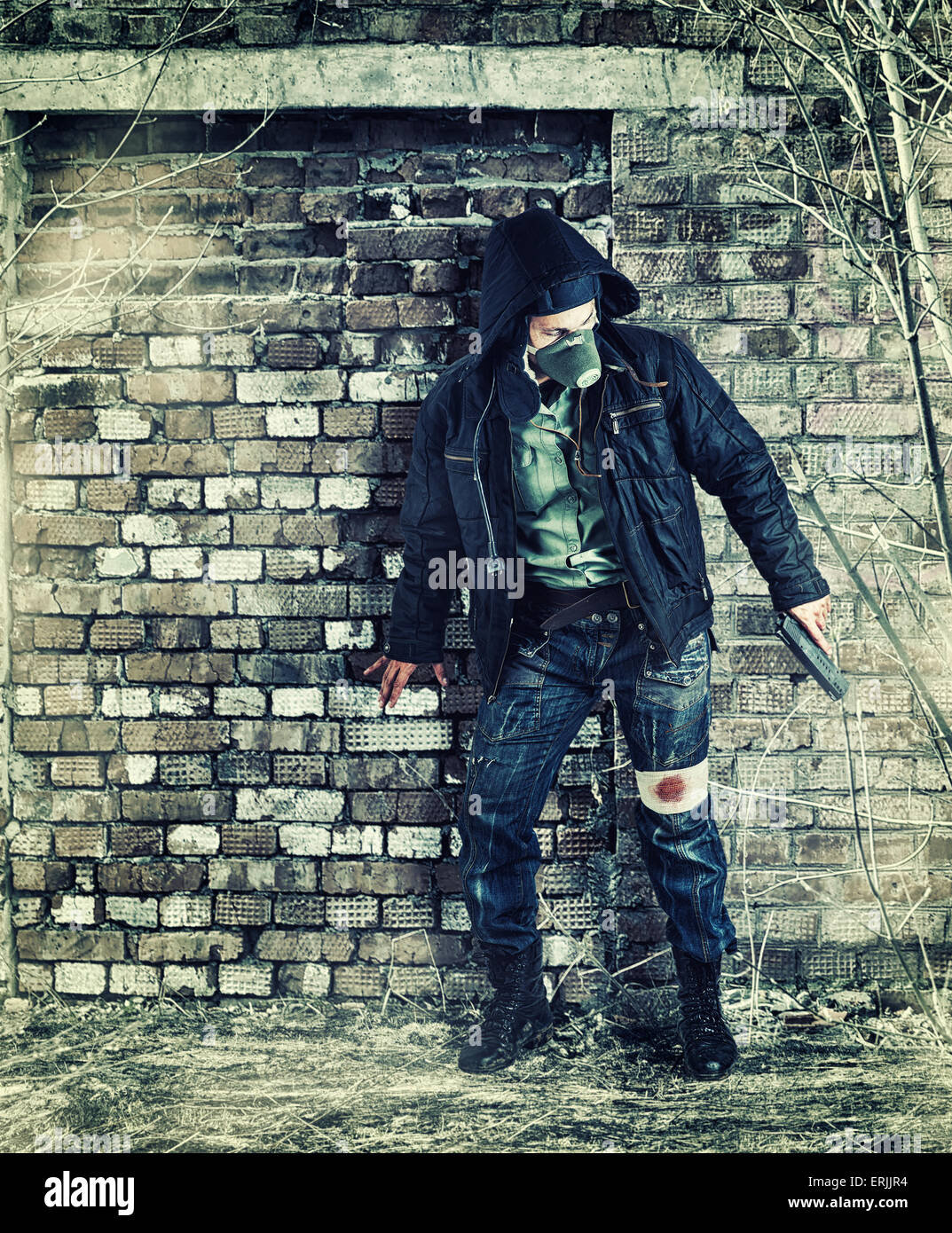 Environmental disaster. Post apocalyptic survivor in gas mask holding hand gun - Stock Image