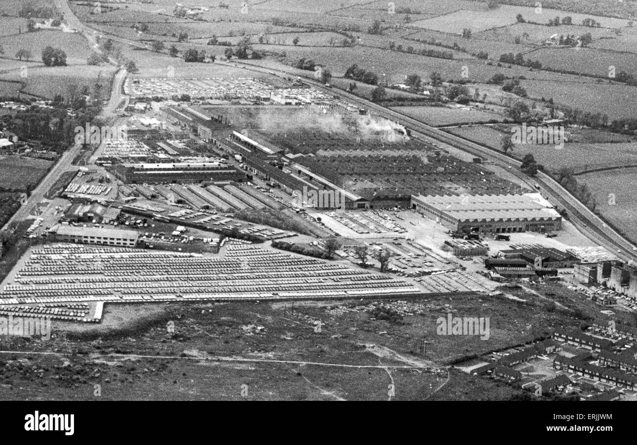 The Chrysler works at Ryton. The pattern of the factory roofs contrasts with that of the mass of cars in the foreground. - Stock Image