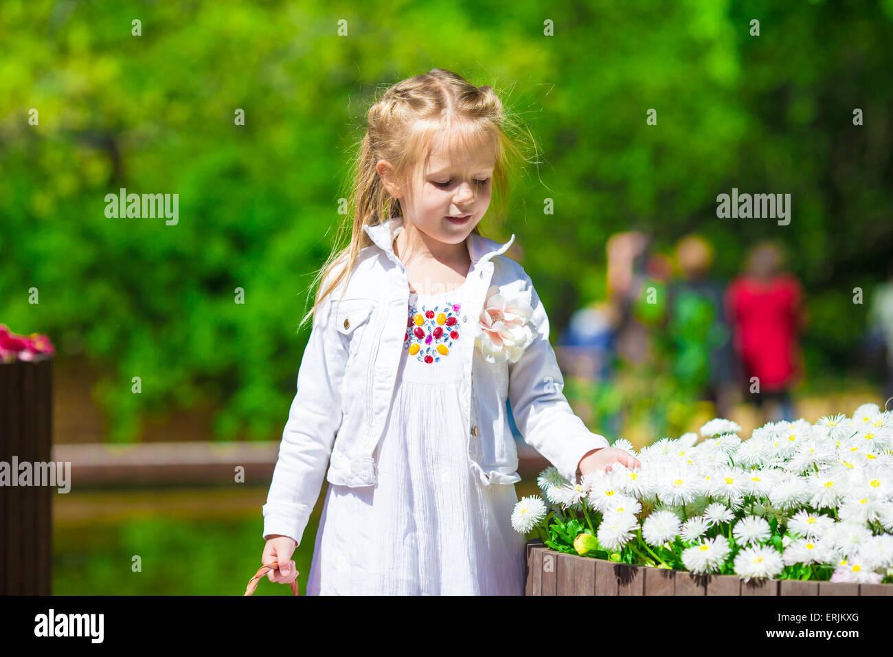 Spring garden, spring flowers, dorable little girl and tulips - Stock Image