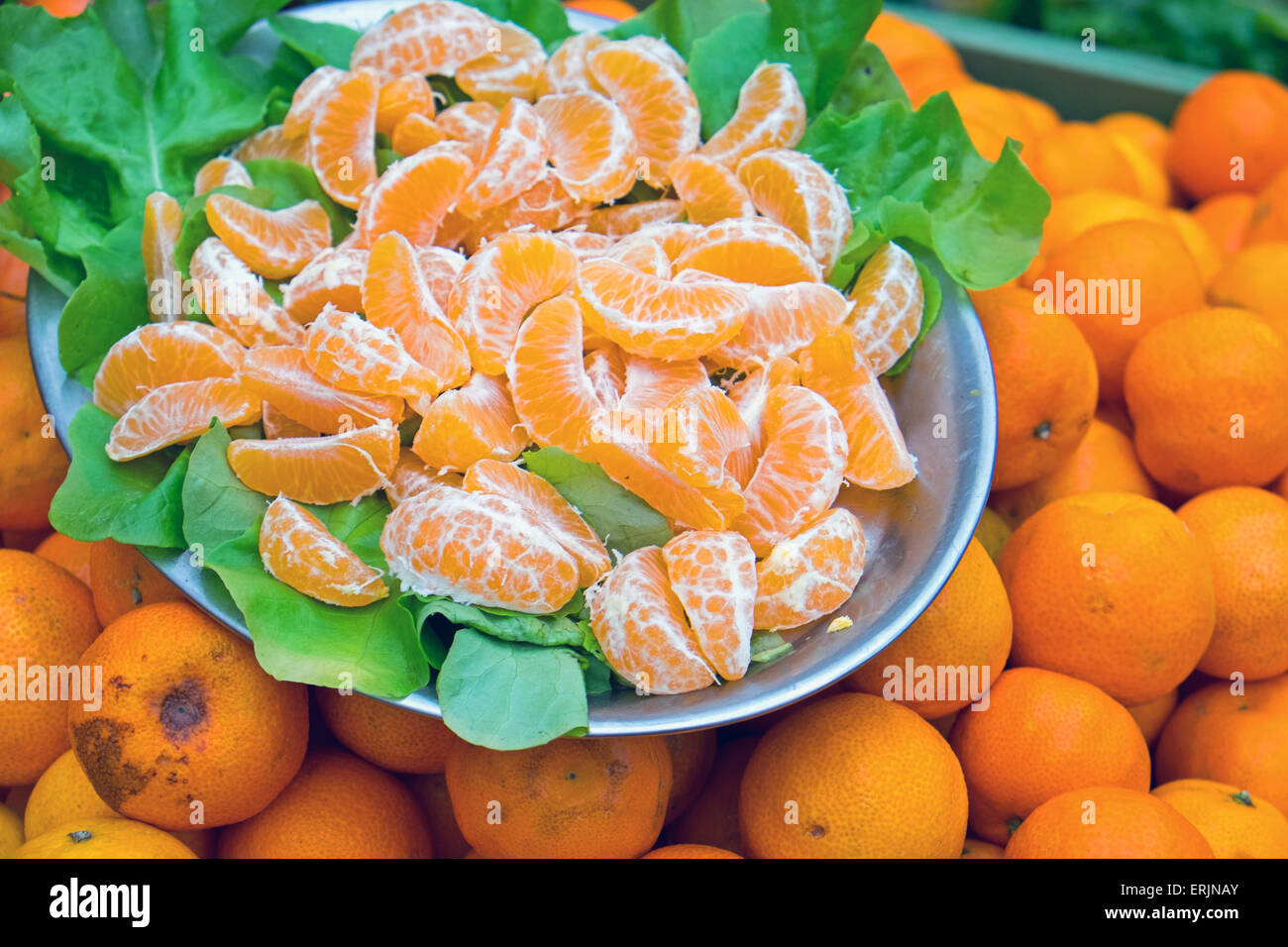 Clemetine slices on a plate seen on a market - Stock Image