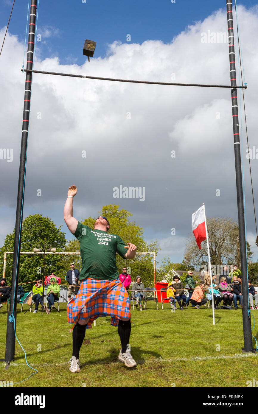 Man throwing the weight over the bar, a traditional style of game during a Highland Games meeting, Carmunnock, Glasgow, - Stock Image