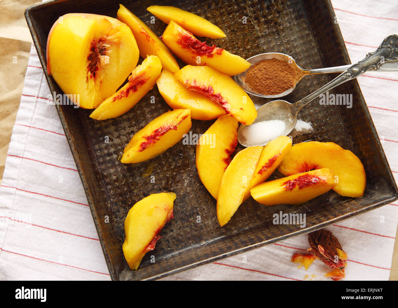 Fresh peach slices with spoonfuls of cinnamon and sugar on a vintage pan - Stock Image