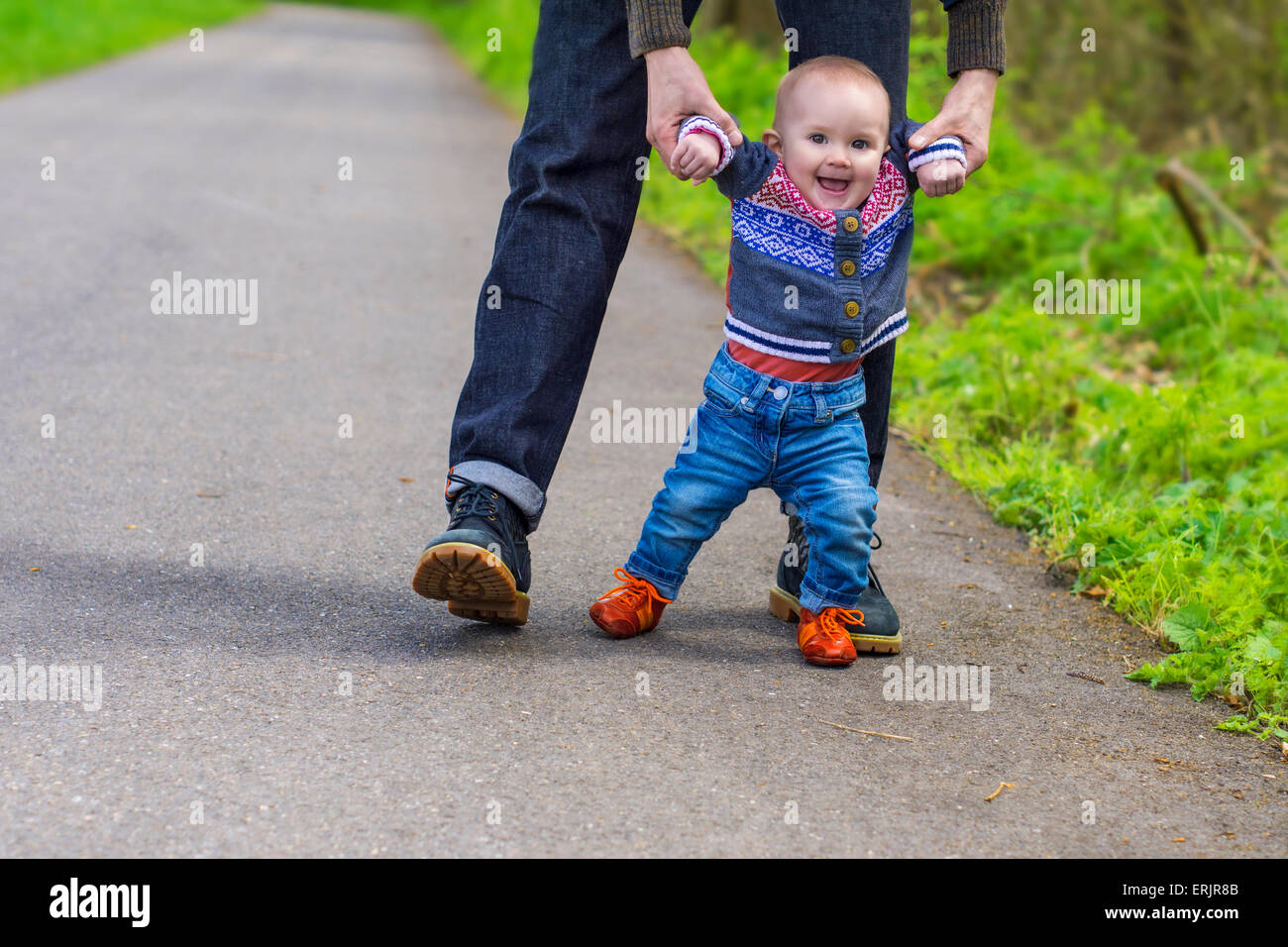 Father guiding his baby with the first steps - Stock Image