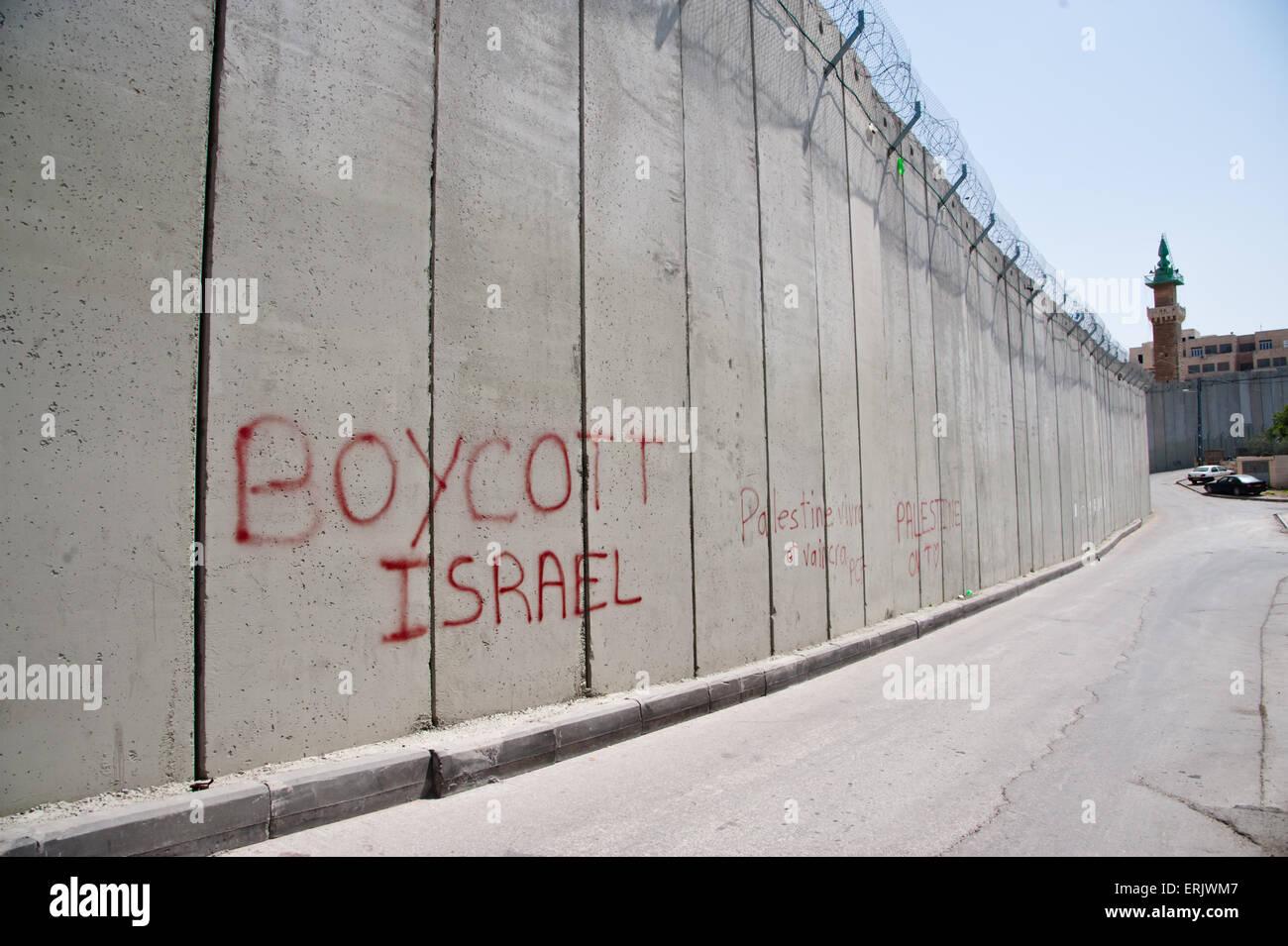 Graffiti on the Israeli separation barrier dividing the East Jerusalem neighborhood of Abu Dis reads, 'Boycott - Stock Image