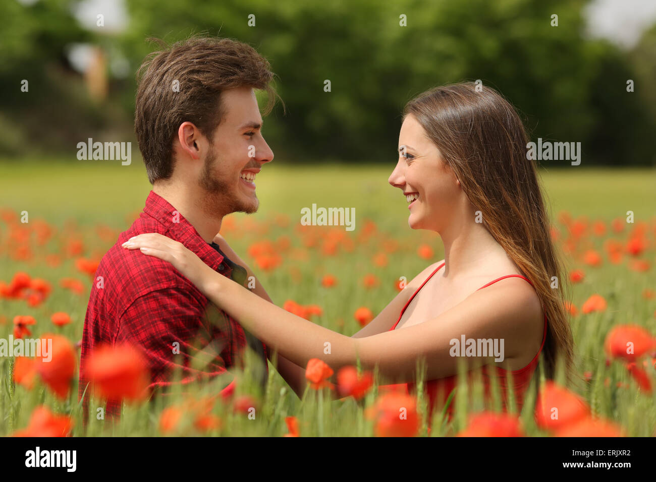 Happy couple looking each other affectionate in a field with red poppy flowers Stock Photo