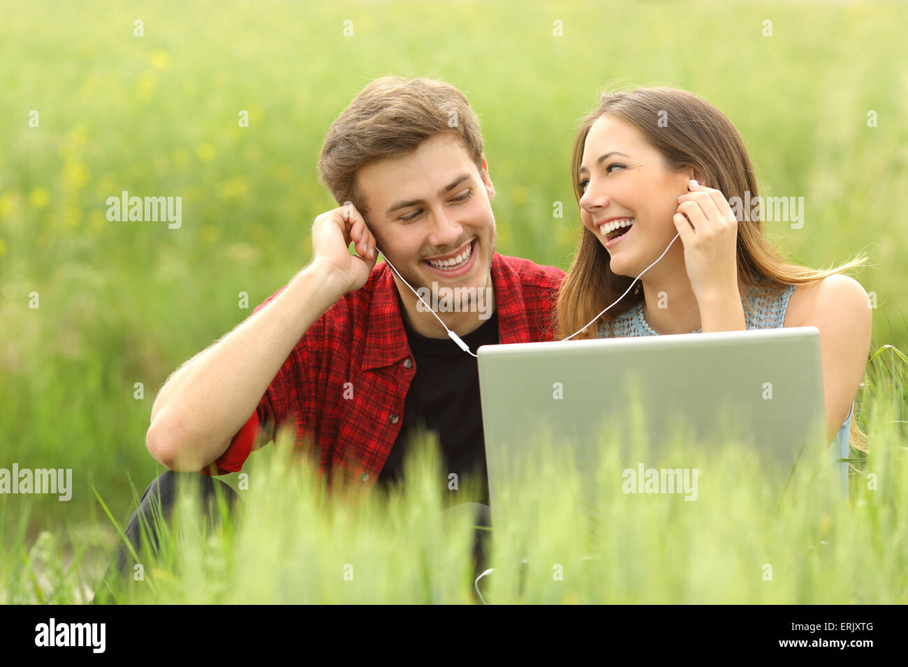 Happy couple or friends sharing music from a laptop sitting in a green field and looking each other - Stock Image