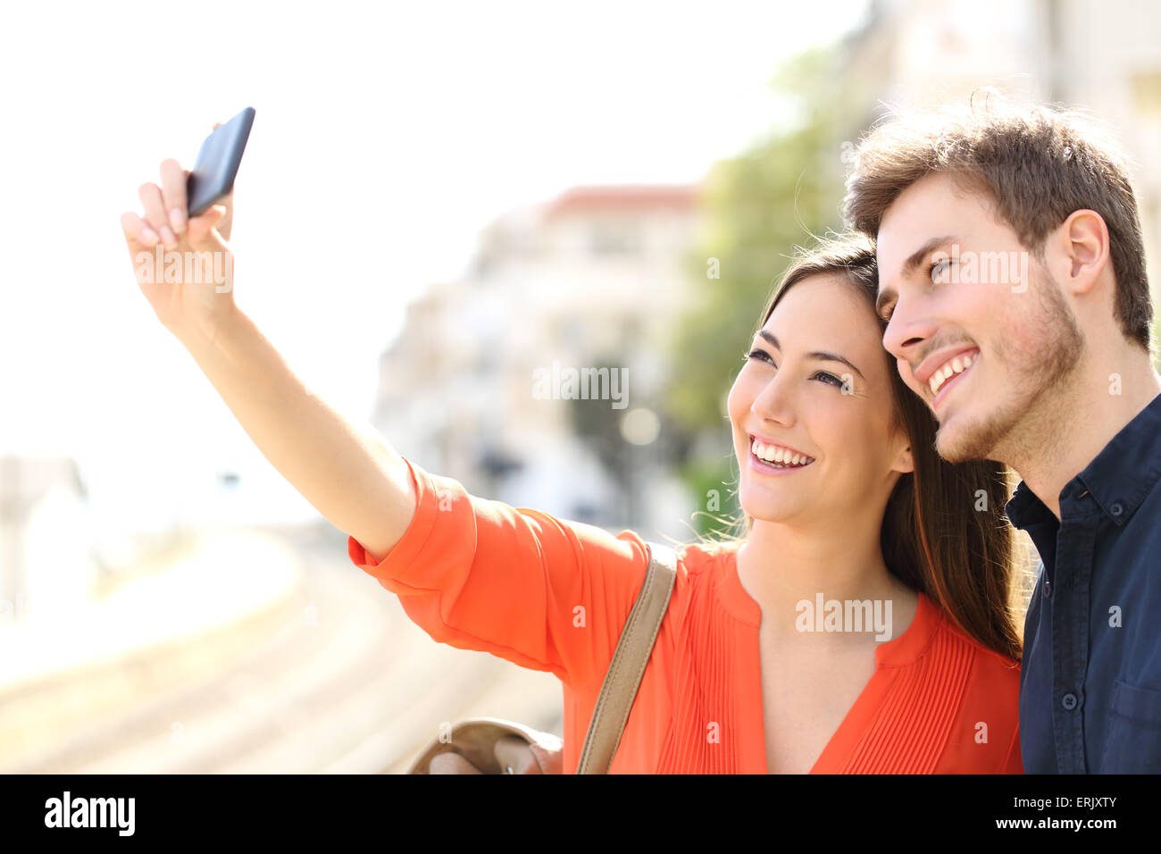 Traveler tourists couple photographing a selfie in a train station - Stock Image
