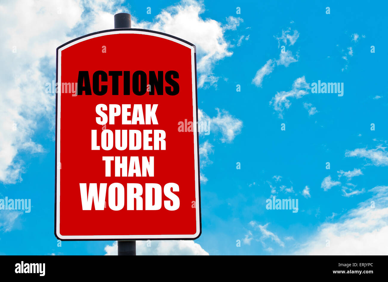 Actions Speak Louder Than Words motivational quote written on red road sign isolated over clear blue sky background. Stock Photo