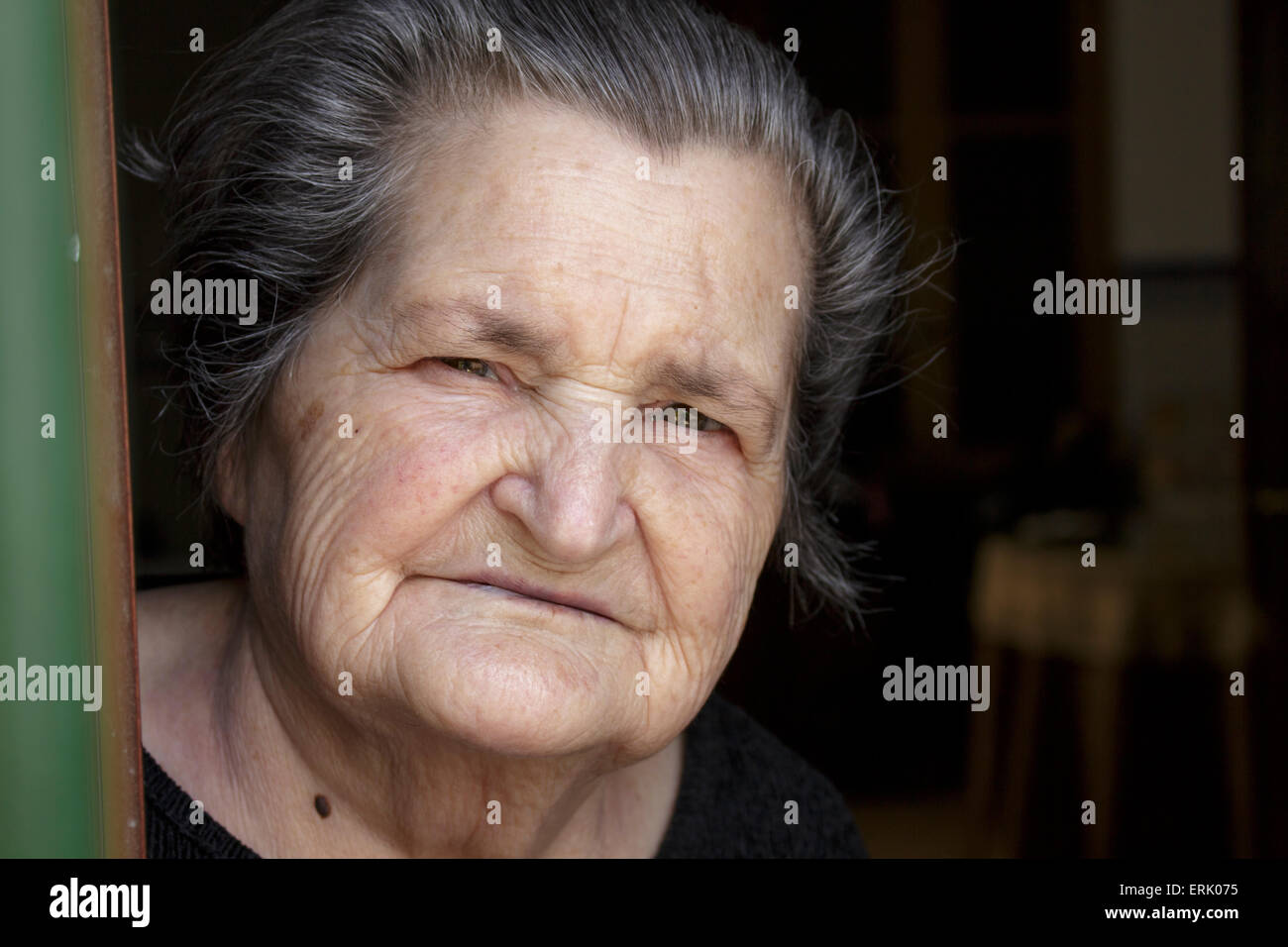 An elderly dressed in mourning looks at the camera from her home's window, in a little andalusian town - Stock Image