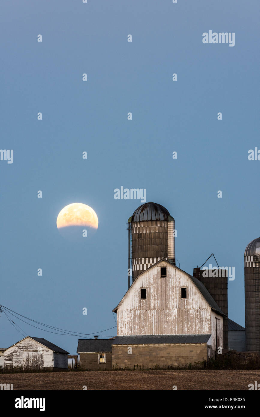 Partial lunar eclipse over farm buildings near Shakopee, Minnesota. Stock Photo
