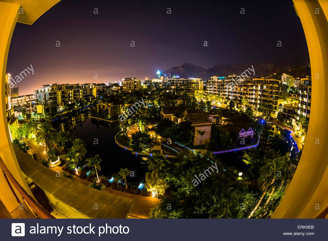 View From Balcony At Night With Apartment Buildings And Table Stock