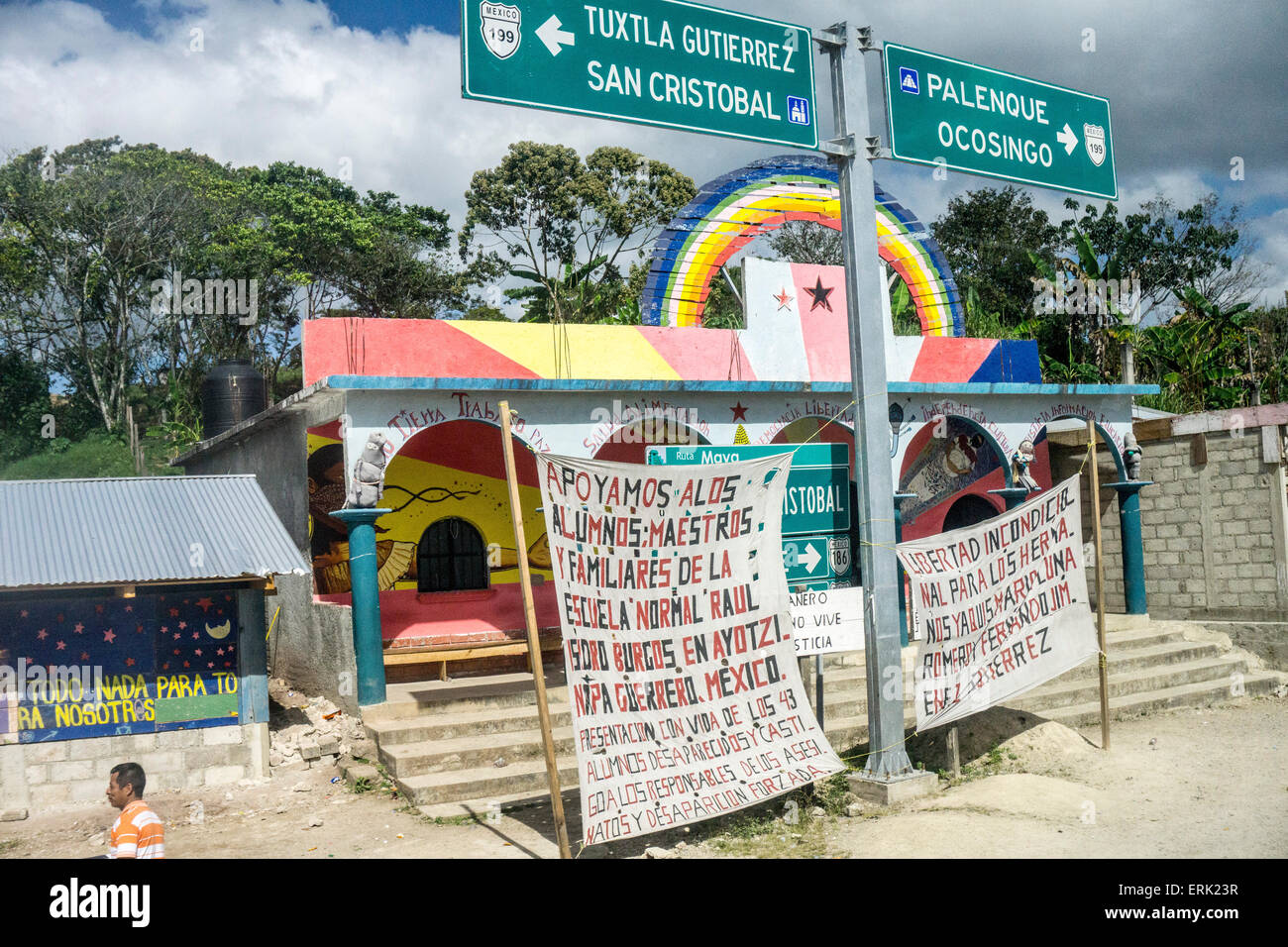 federal highway sign at intersection in Chiapas helps support Zapatista  banners protesting inaction on 43 disappeared - Stock Image