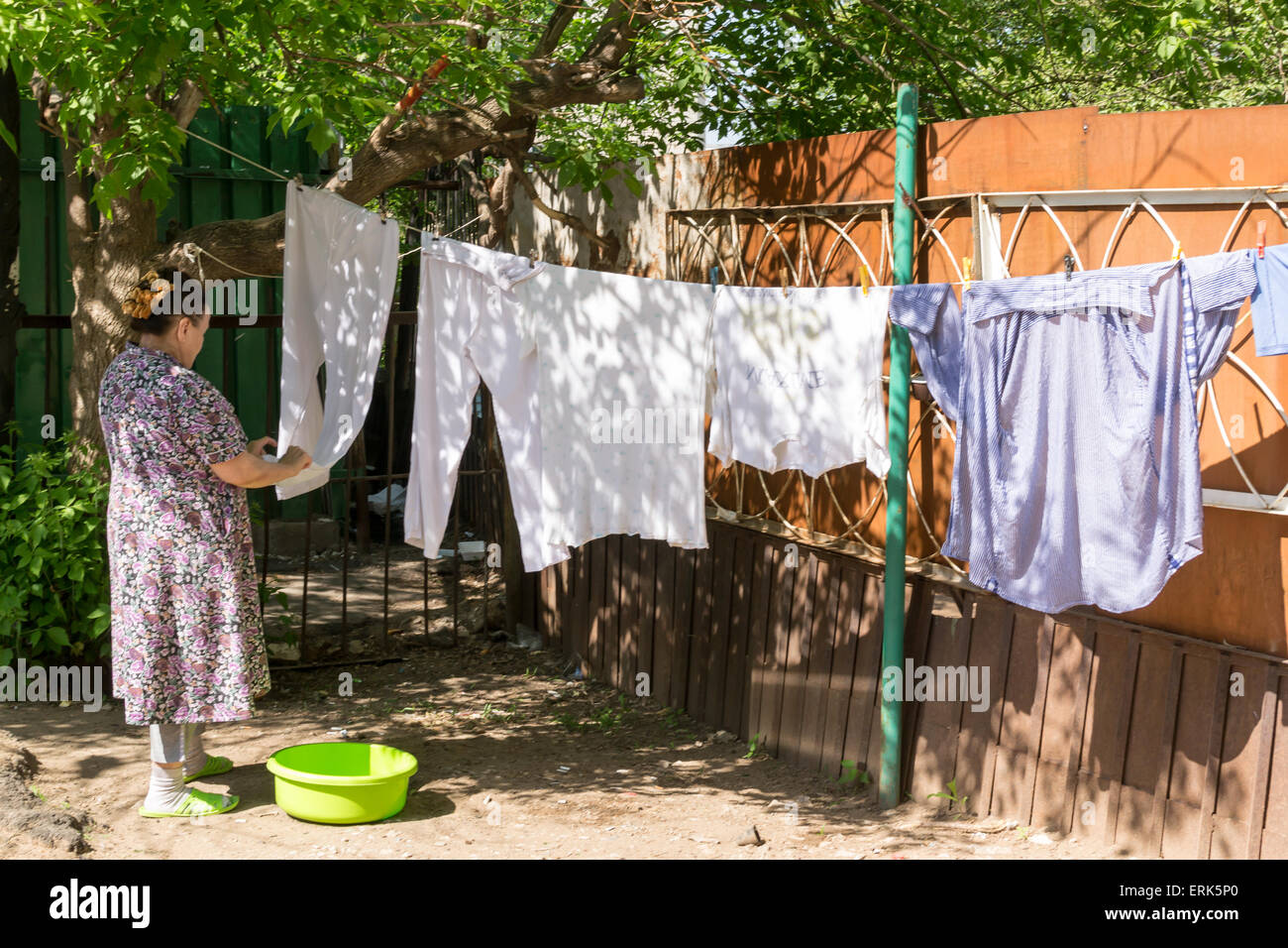 Old pensioner woman making the most of a hot summer hanging up her washing in Ufa Russia - Stock Image