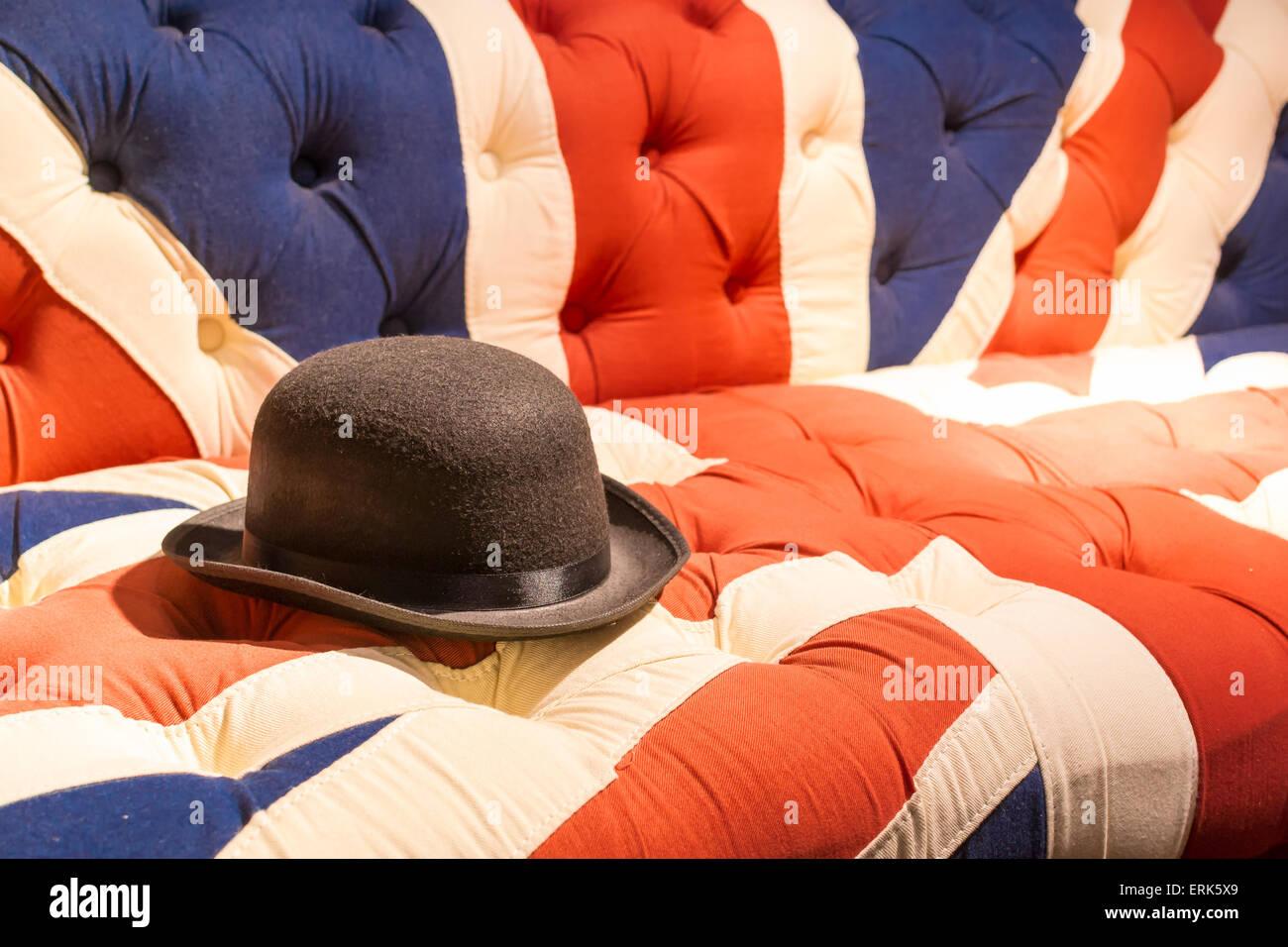 Union Jack Flag style modern cushioned sofa with black felt bowler hat - Stock Image