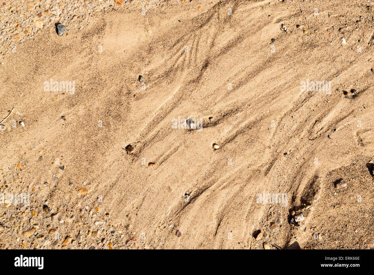 Sand wash from rain water with stones and trails - Stock Image