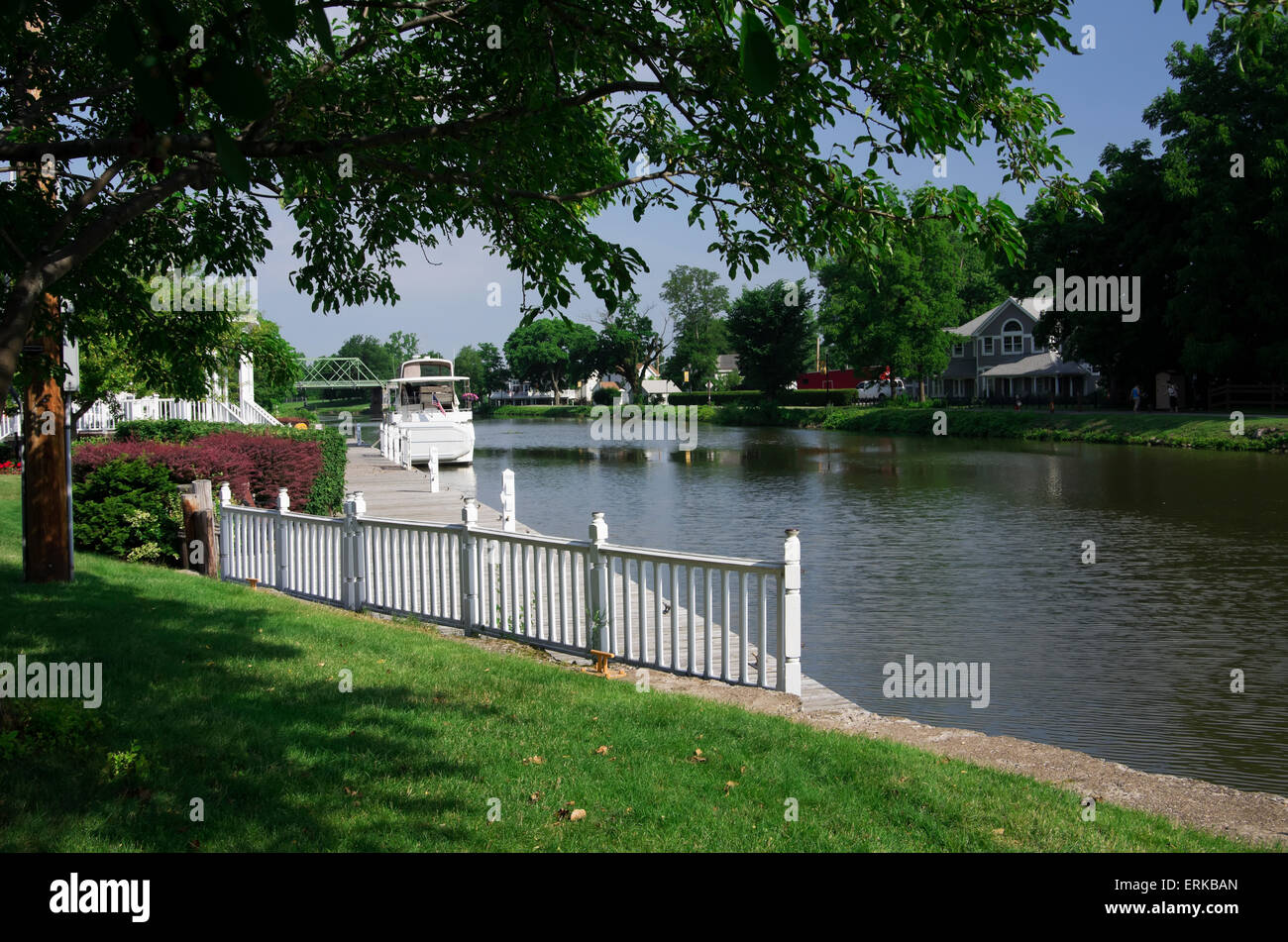 Private yacht tied along canal side and green lawn; Spencerport, New York, United States of America - Stock Image