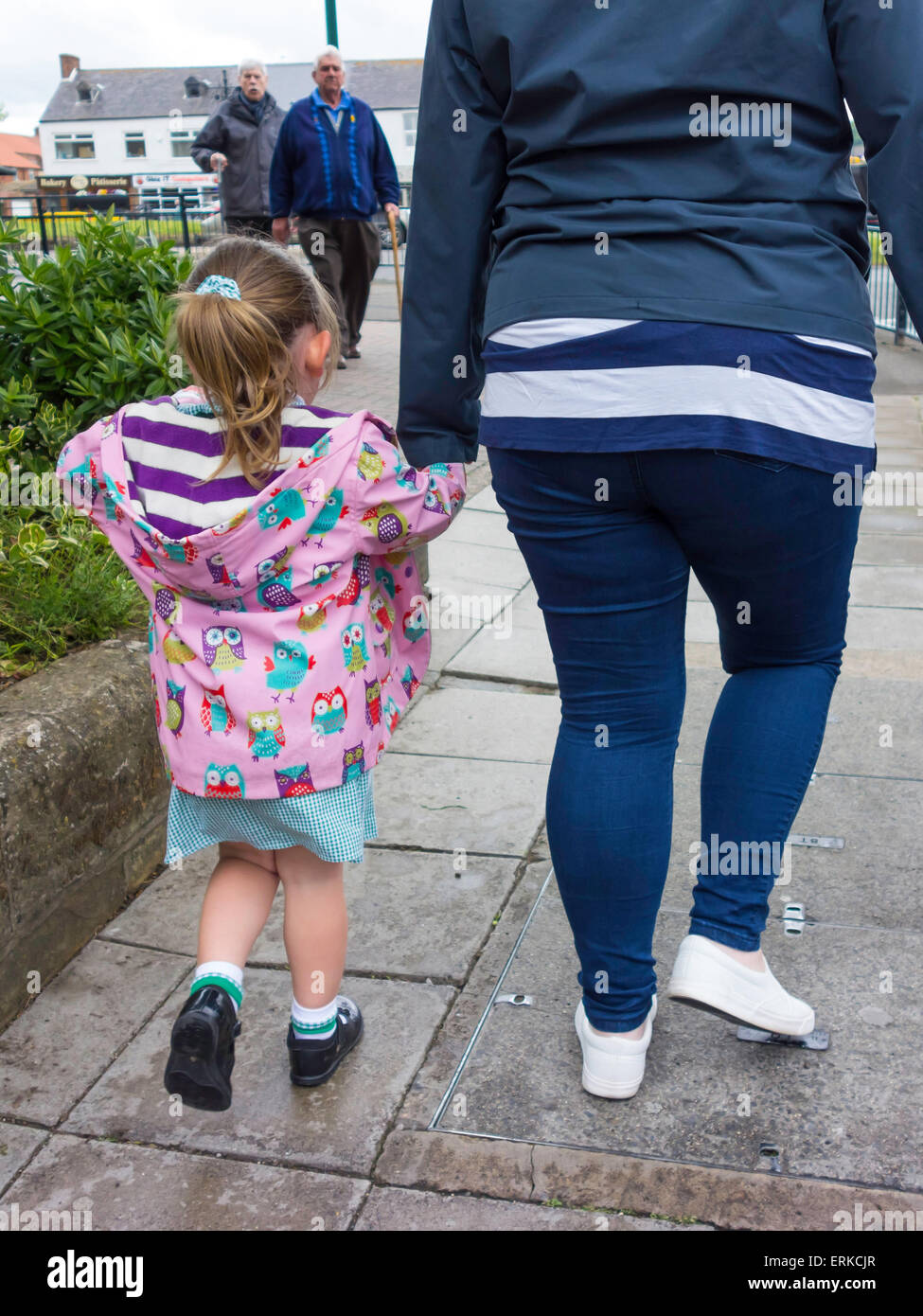 Rear view of a mother holding the hand of a young girl going home from school - Stock Image