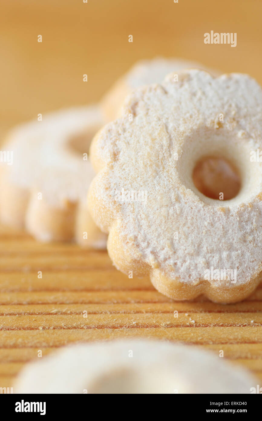 Italian butter biscuits piled on a wooden table. These cookies have a flower shape and covered with icing sugar - Stock Image